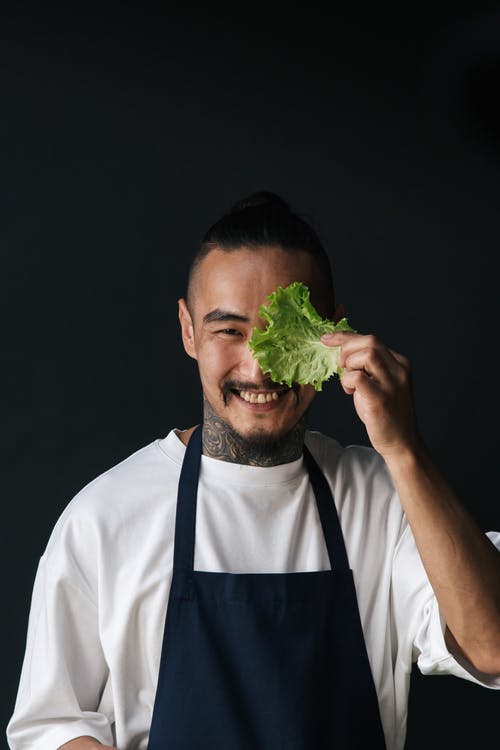 A Happy Male Chef Holding a Lettuce while Looking at Camera