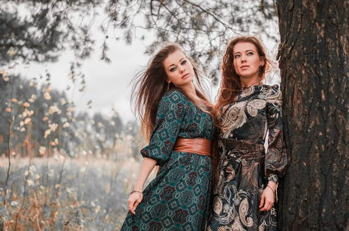 2 Women in Black and Red Floral Dress Standing Near Bare Trees