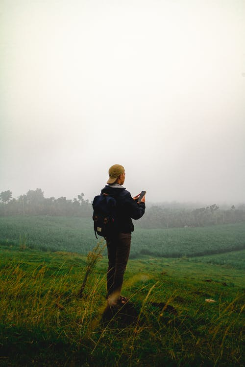 Man in Black Jacket Standing on Green Grass Field During a Foggy Day