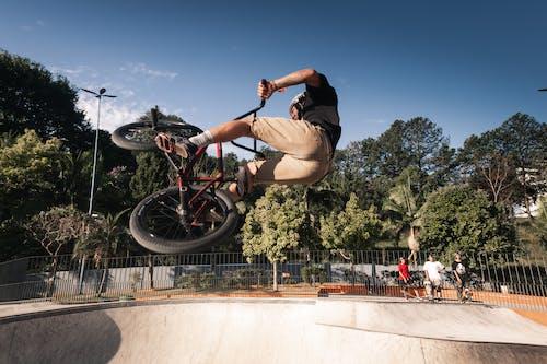 Man in Black T-shirt and Brown Shorts Riding Red Bmx Bike Doing Stunts