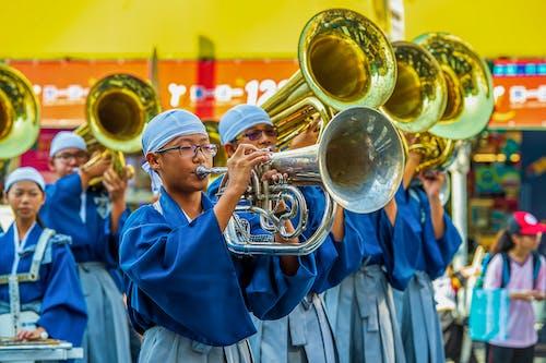 Man in Blue Academic Dress Holding Brass Trumpet