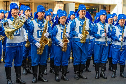 Group of Men in Blue Long Sleeve Shirt Holding Brass Saxophone