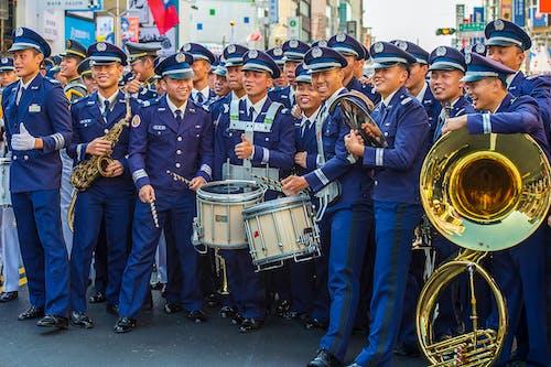 Group of Men in Blue Uniform Playing Drum Set