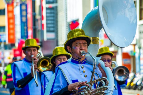 Man in Blue and White Long Sleeve Shirt Playing Trumpet