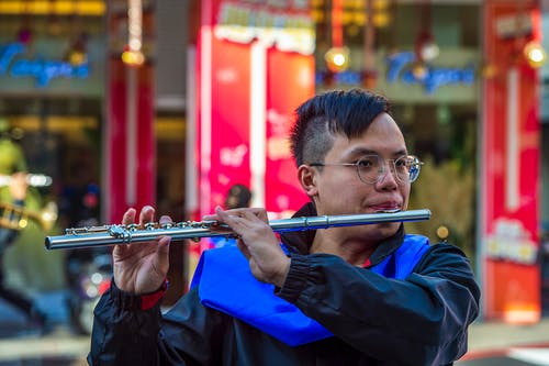 Man in Blue Jacket Playing Flute