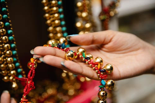 Close-Up Shot of a Person Holding a Gold Beaded Necklace