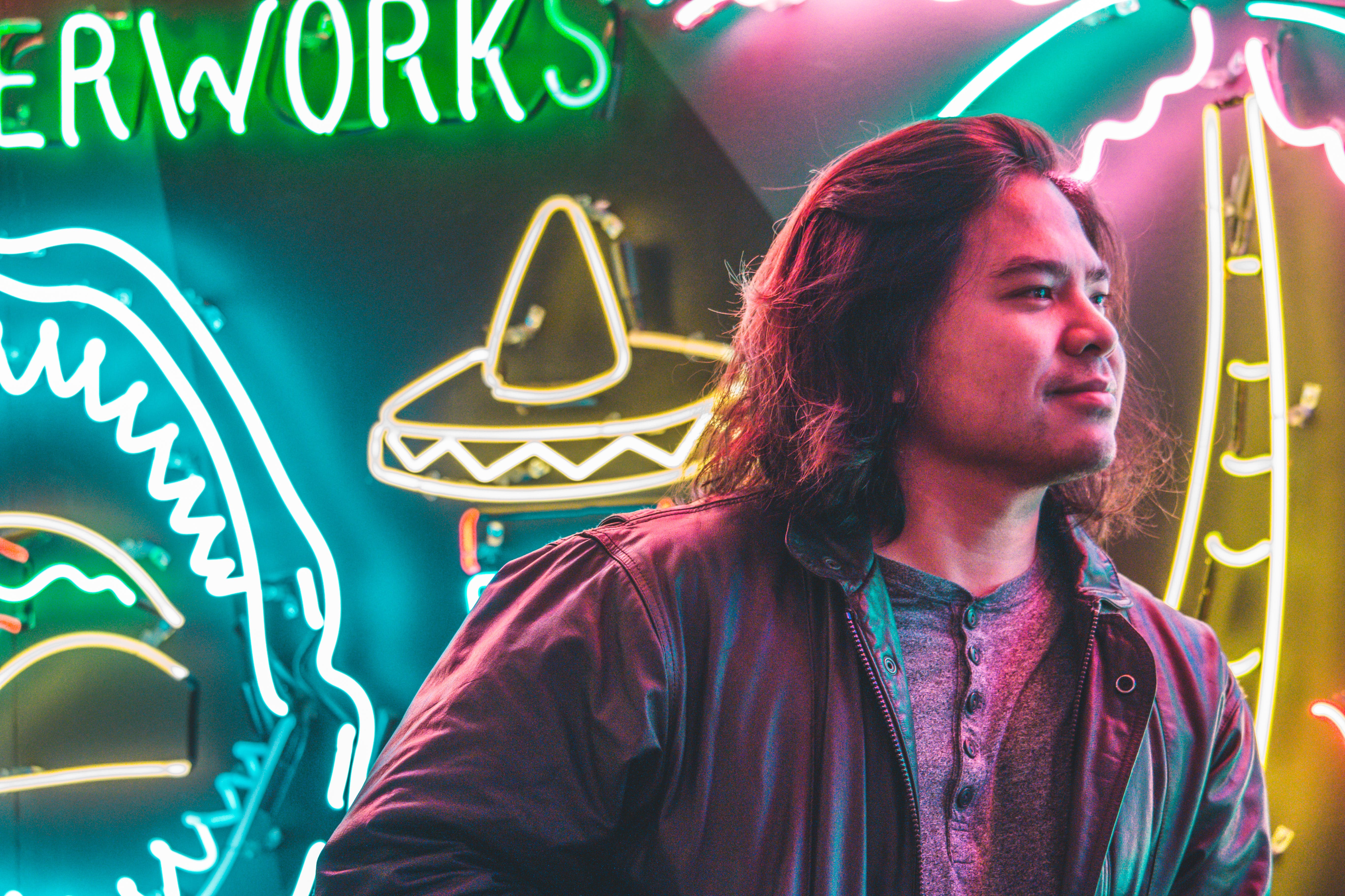 Man Standing in Front of Neon Signages