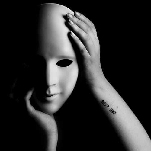 Grayscale Photo of Person Holding a Mask