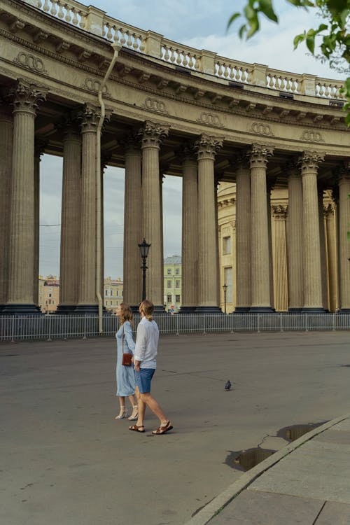 Couple Looking At Columns Of A Historical Building