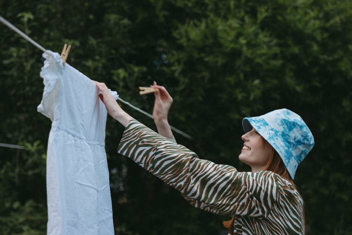Woman Hanging A Dress on Clothesline For Drying
