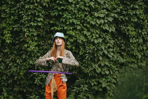 Woman in Leopard Print Dress Shirt and Orange Pants Using A  Hula Hoop