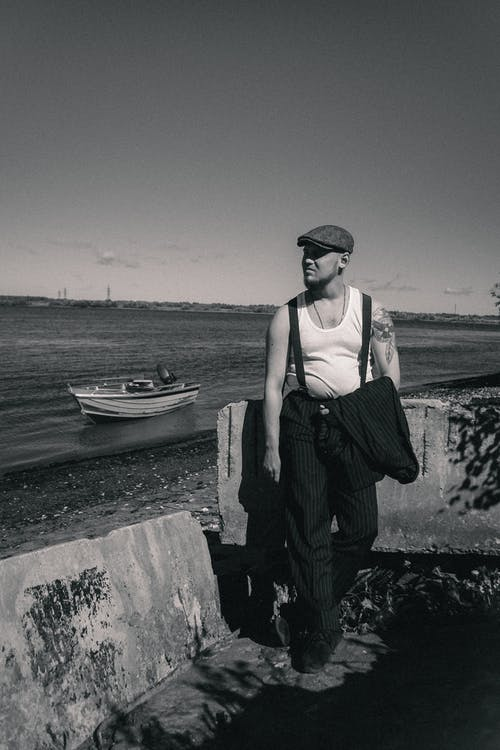 A Man Holding His Coat while Near a Coast