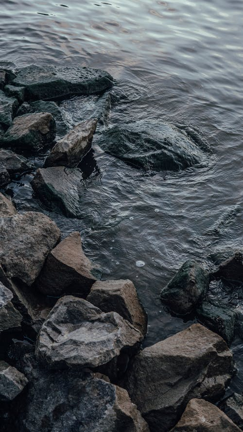 Brown and Gray Rocks on Body of Water