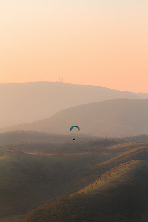 Person in Parachute over the Mountains