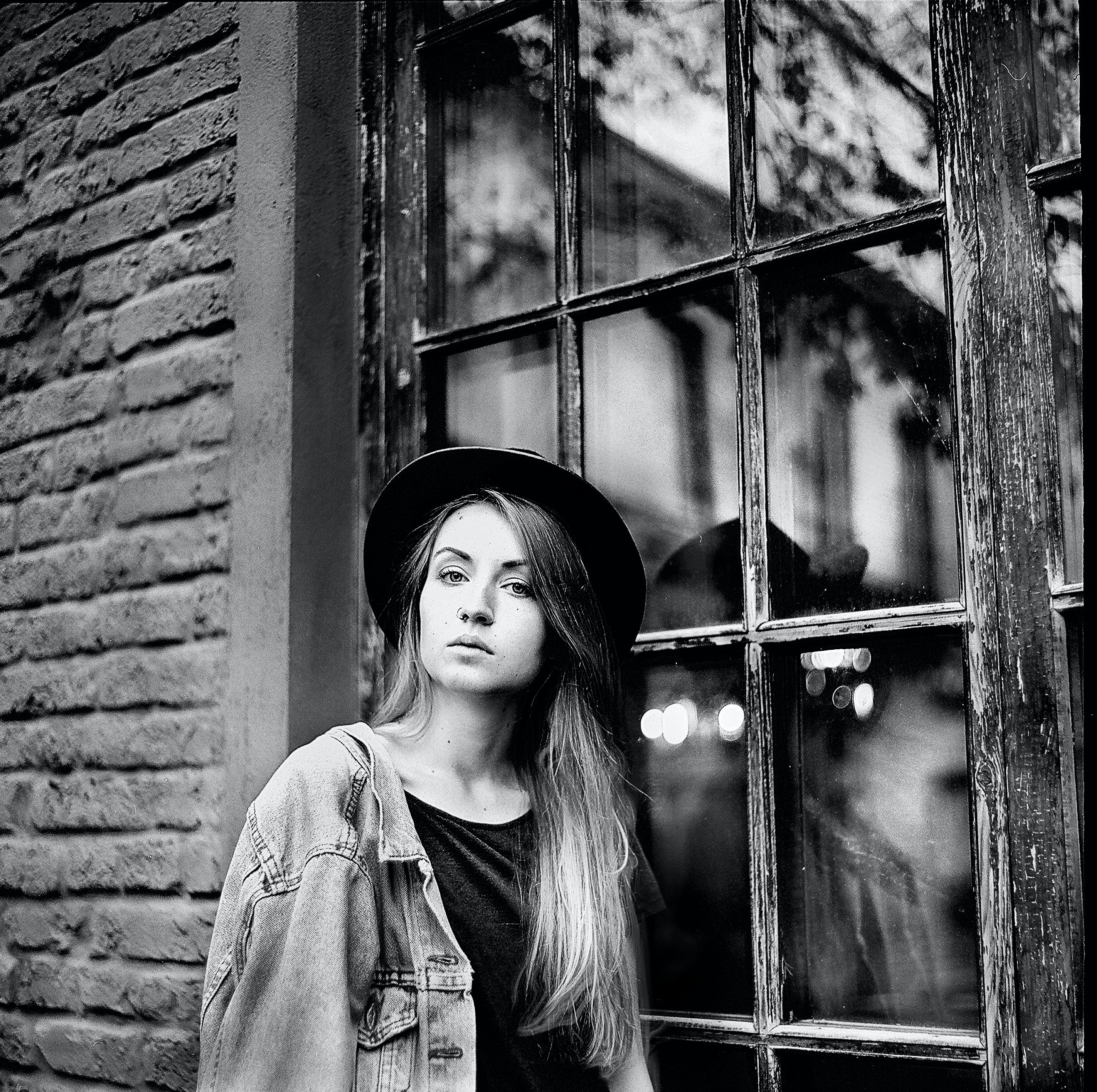 Grayscale Photo of Women's Denim Jacket and Hat Leaning on Window