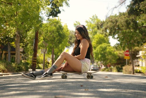 Woman in Black Tank Top and White Shorts Sitting on Gray Concrete Pavement