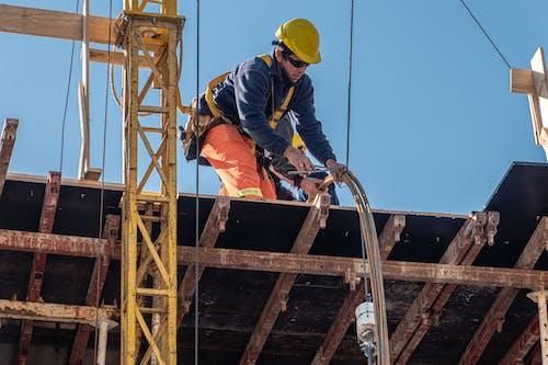 Man in Yellow Hard Hat and Orange Jacket Climbing on Yellow Metal Ladder