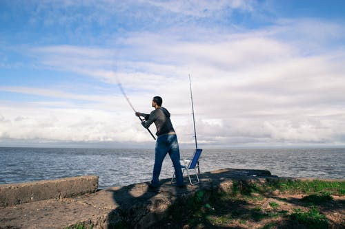 Man in Blue Shirt and Blue Denim Jeans Holding Fishing Rod Standing on Brown Rock during