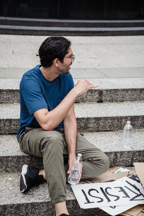 Man in Blue Shirt Sitting on Concrete Steps