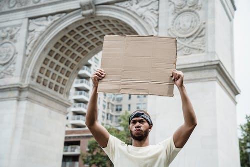 A Man Holding a Placard Near the Washington Square Arch