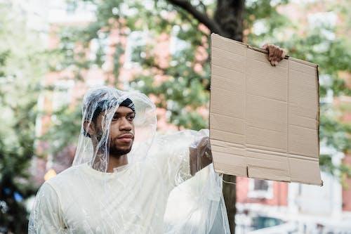 A Man in a Transparent Raincoat Holding a Cardboard Placard