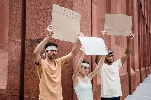 Protesters in Bandanas Holding Cardboard Placards