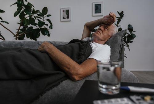 A Sick Elderly Man Lying Down on Sofa
