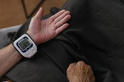 A Person Measuring His Own Blood Pressure Using a Wrist Blood Pressure Meter