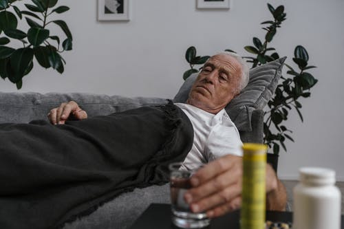 A Sick Elderly Man Lying Down on Sofa while Holding a Drinking Glass