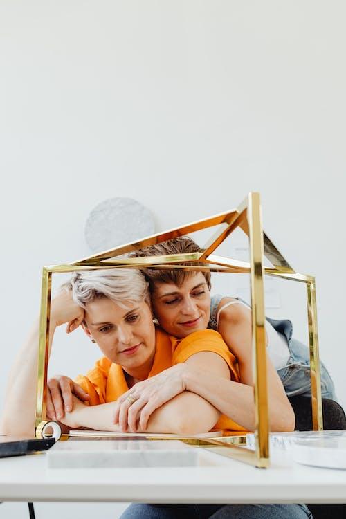 Woman in Orange Shirt Lying on Bed