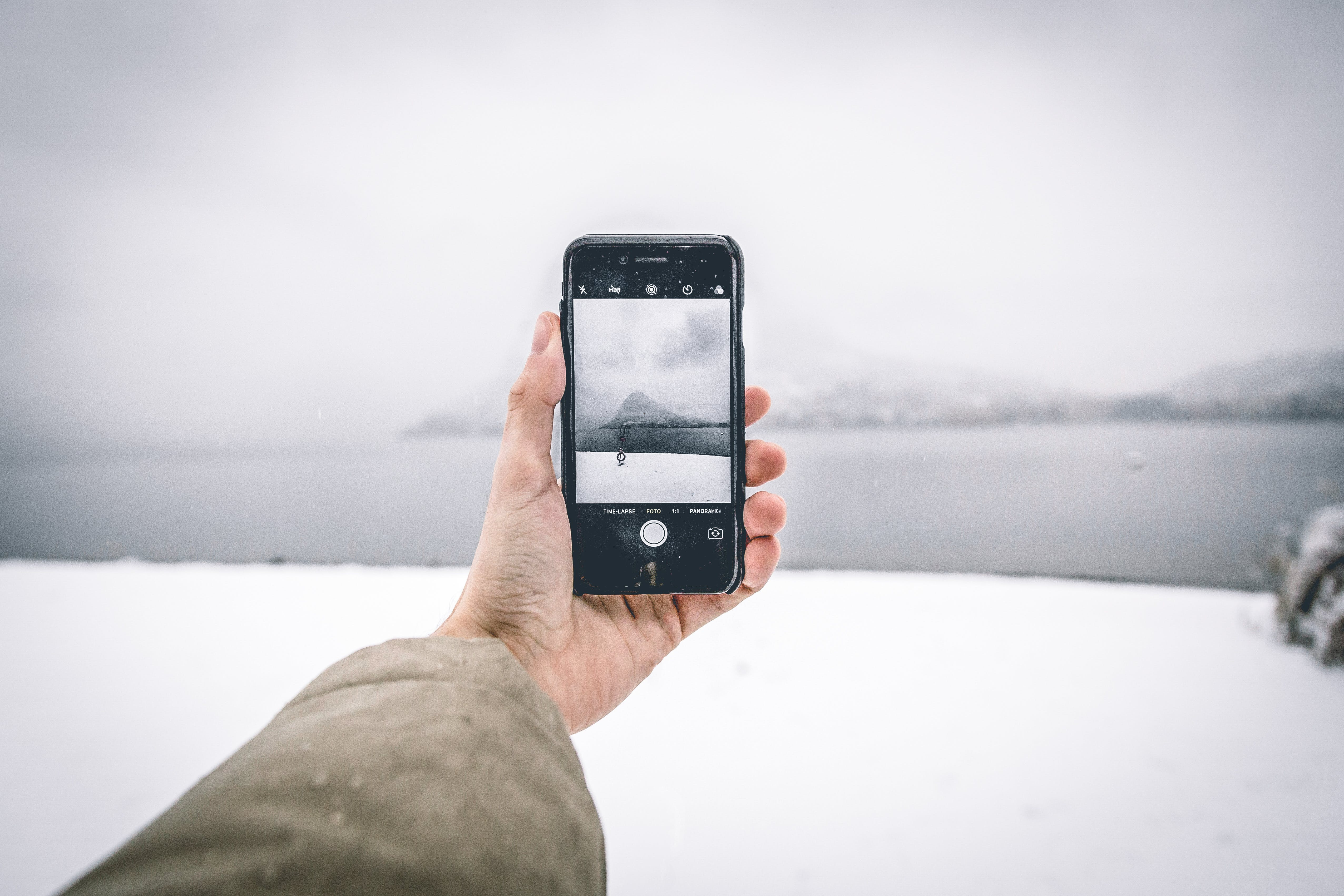 Photo of Person Wearing Brown Coat Holding Android Smartphone While Taking Picture of Mountain and Body of Water