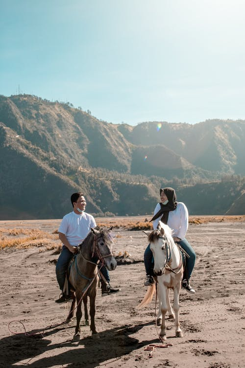 Man in White Shirt Riding Horse on Brown Sand