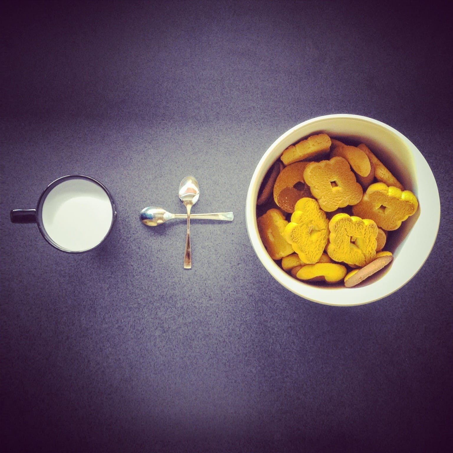 Crackers in Round White Ceramic Cup Near Two Stainless Steel Spoons and Black Ceramic Mug