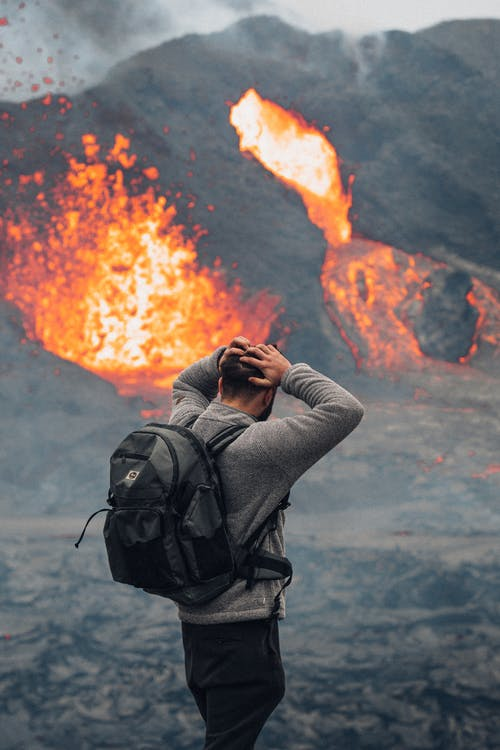 Man in Gray Jacket Taking Photo of Orange Fire