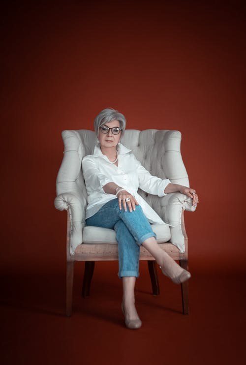 Woman in White Long Sleeve Shirt Sitting on White Sofa Chair