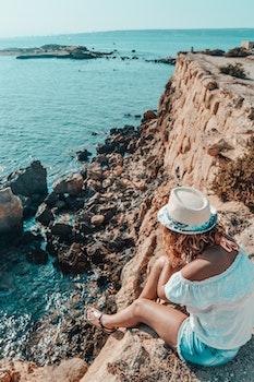 Woman Sitting in Stone Near Body of Water