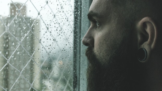 Selective Focus Photography of Man Staring on Glass Window Filled With Droplets