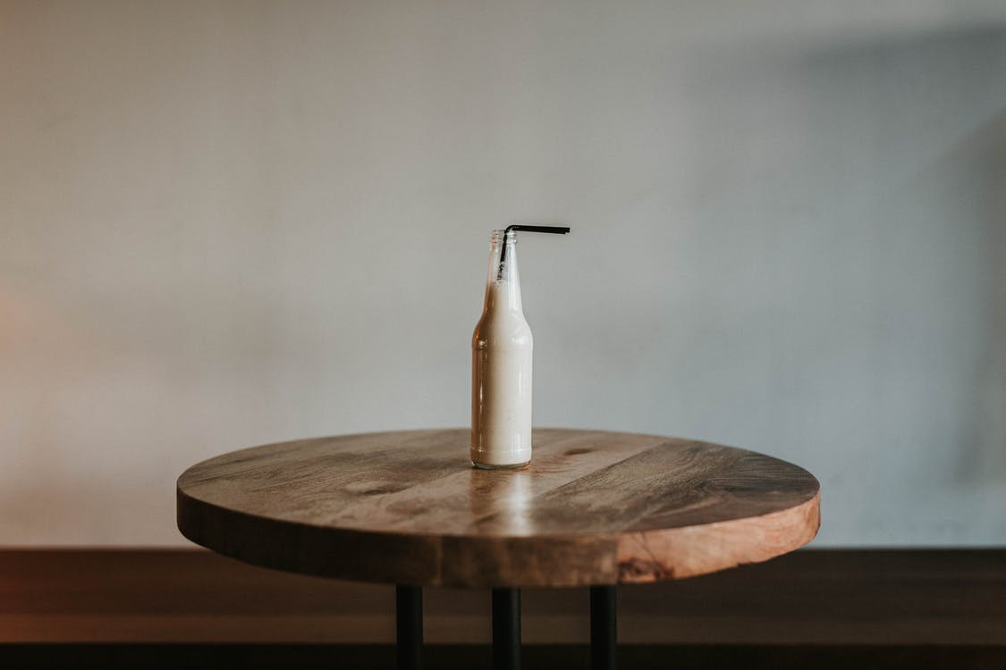 Glass Bottle Filled With Black Straw on Brown Wooden Table