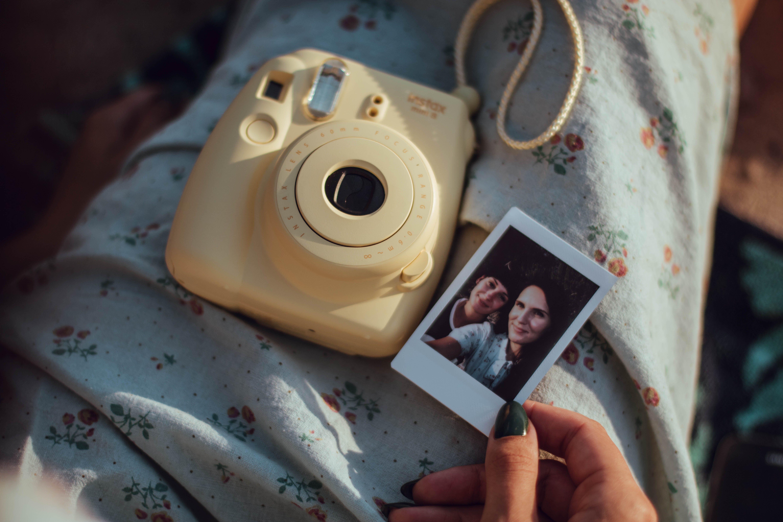 Person Holding Woman's Photo Beside White Fujifilm Instant Camera