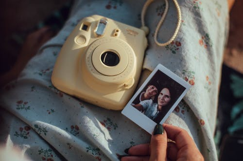 Person Holding Woman's Photo Beside White Fujifilm Instant Camera