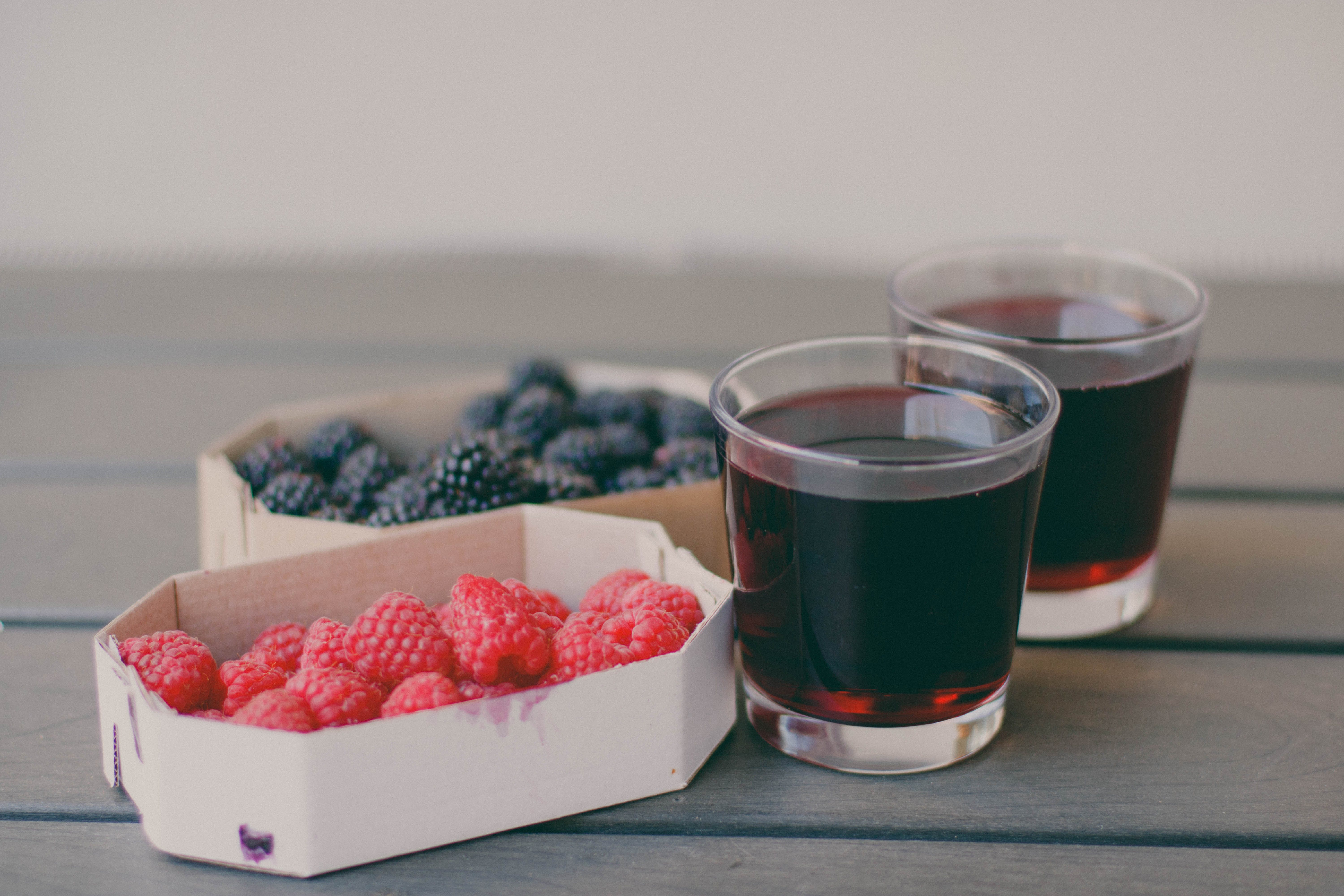 Two Drinking Glasses Filled With Raspberry and Blueberry Fruit Juices