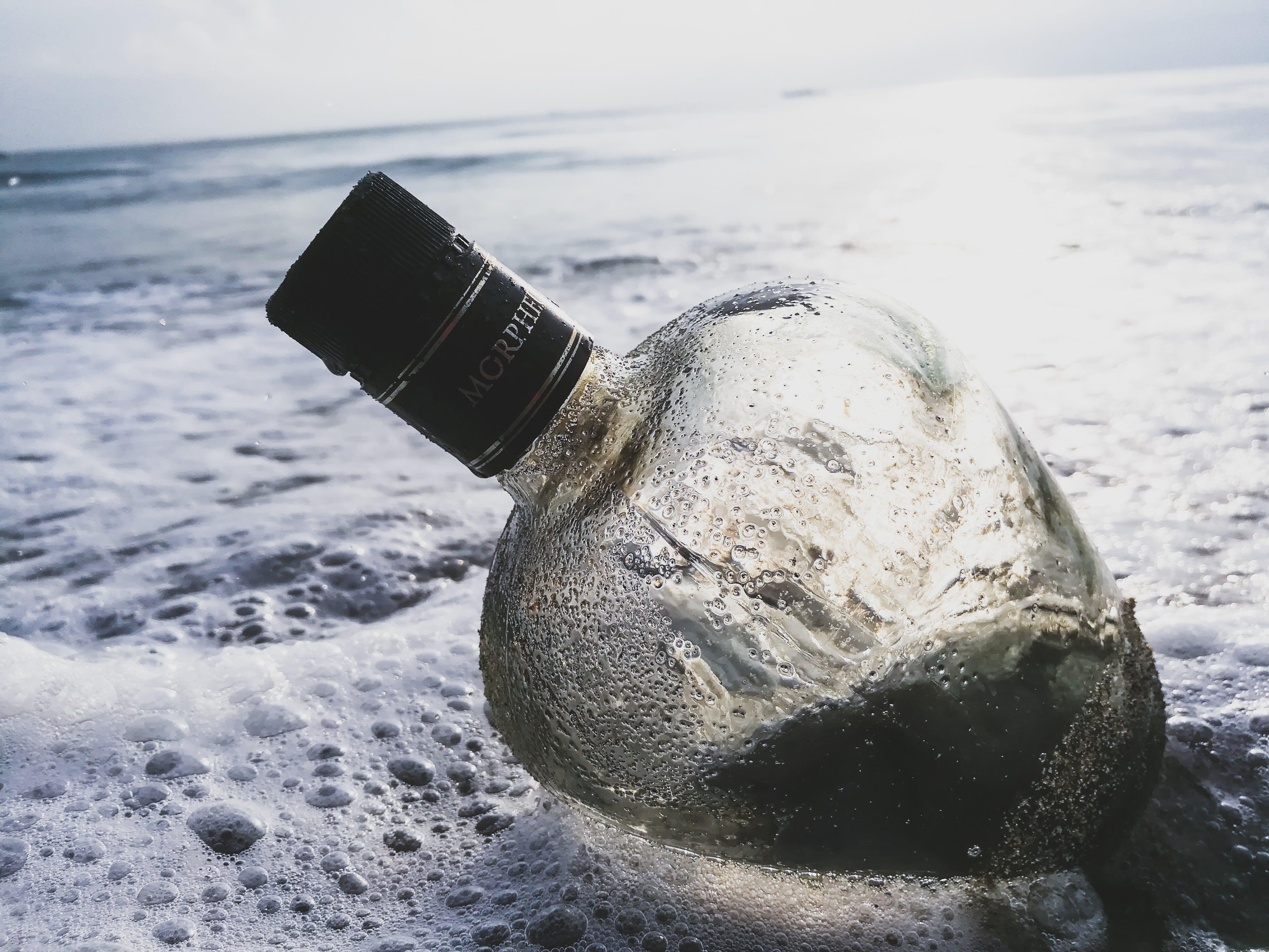 Clear Glass Bottle on Body of Water