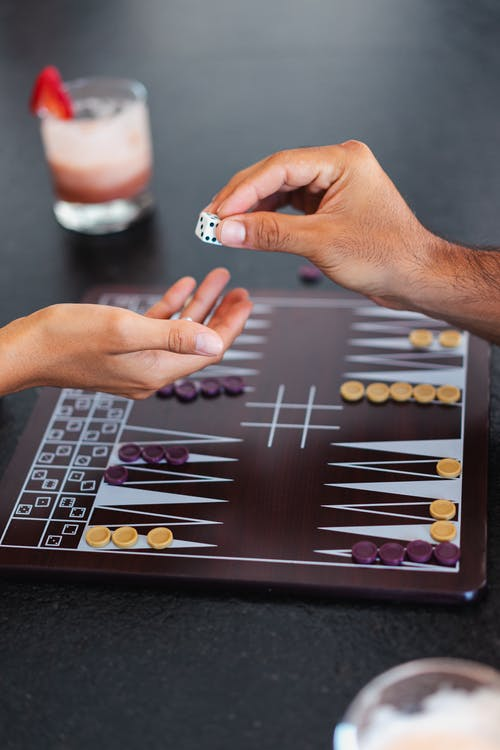 Person Holding a Dice Playing Board Game