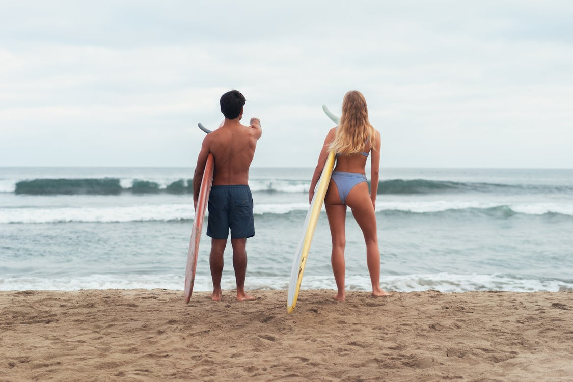 Man and Woman Holding Surfboard While Standing on the Beach