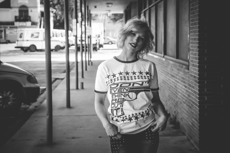 Woman in Crew-neck Shirt Standing Beside Brick Wall Building