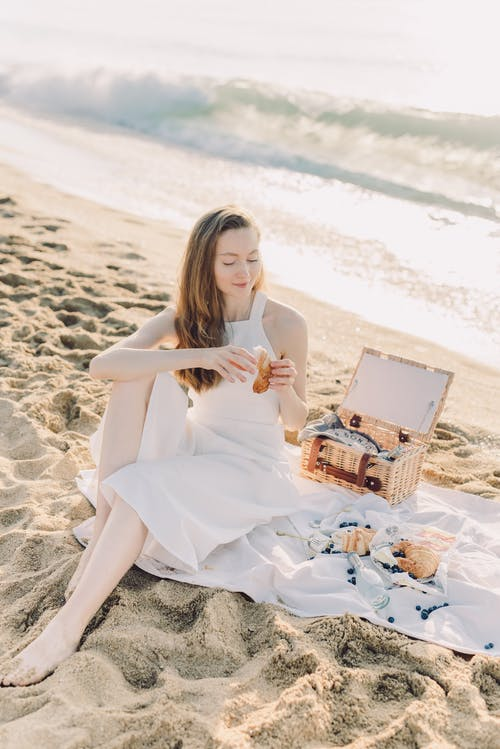 A Woman Having a Picnic Date on the Beach
