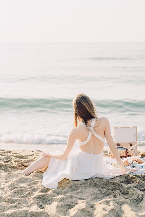 Woman in White Dress Having a Picnic on the Beach