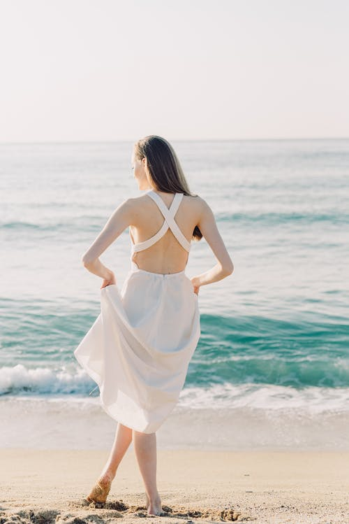 Back View of Woman in White Dress Standing on the Seashore