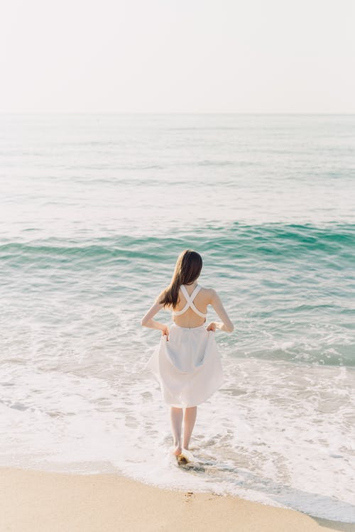 A Woman is Walking Towards the Beach Water