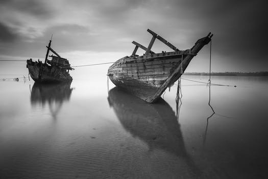 2 boats on the body of water under cloudy sky during daytime in greyscale photo
